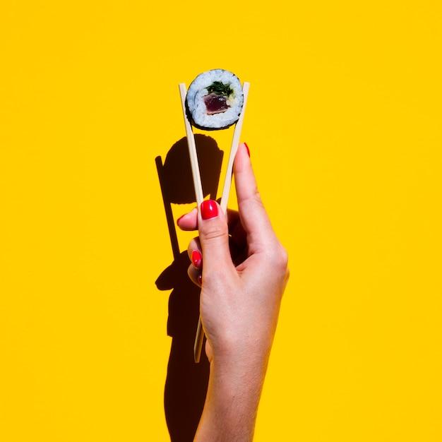 Frau, die essstäbchen mit sushirolle auf gelbem hintergrund hält Kostenlose Fotos