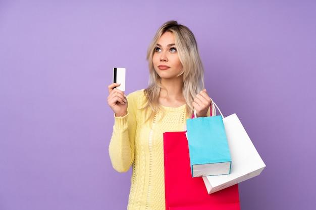 Frau, die etwas kleidung über lokalisierter wand kauft Premium Fotos