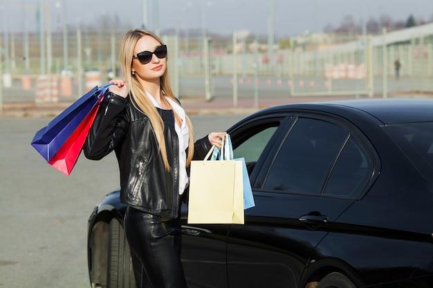 Frau, die farbige taschen nahe ihrem auto in schwarzem freitag-feiertag hält Premium Fotos