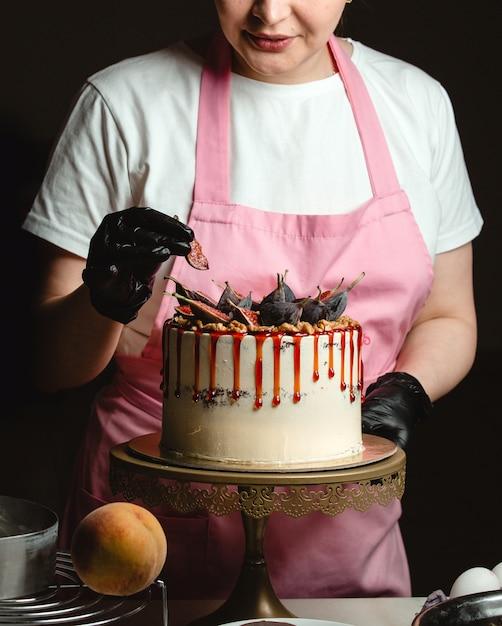 Frau, die feigenstück auf klassischem kuchen hinzufügt, verziert mit feigen und sirup Kostenlose Fotos