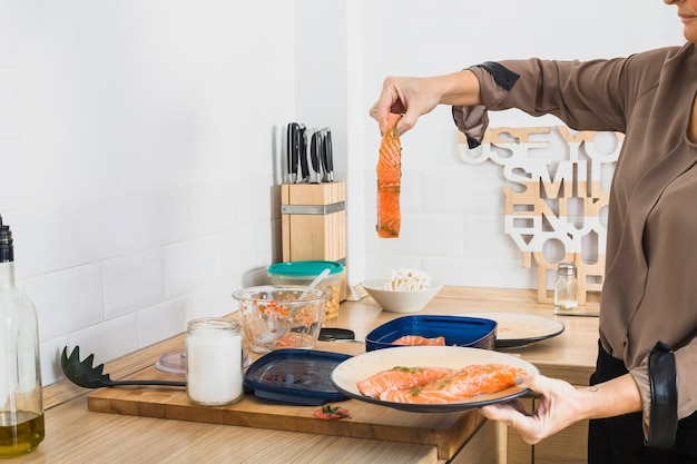 Frau, die fischgericht in der küche kocht Kostenlose Fotos