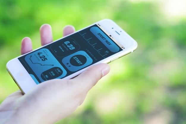 Frau, die fortschritt mit app-gesundheitserfassungstätigkeit auf smartphone überprüft Premium Fotos
