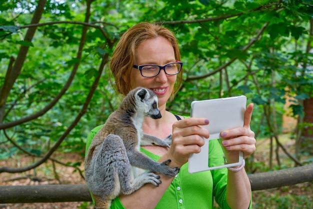 Frau, die foto selfie mit ring angebundenem lemur nimmt Premium Fotos