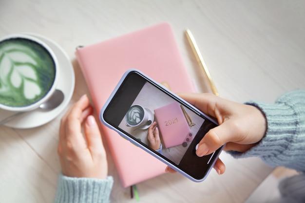 Frau, die foto von blauem kaffee latte, rosa farbigem planer 2021 und goldstift auf ihrem smartphone nimmt. menschen und technik. fotografieren zum posten und teilen in sozialen medien. blogging-konzept. Premium Fotos