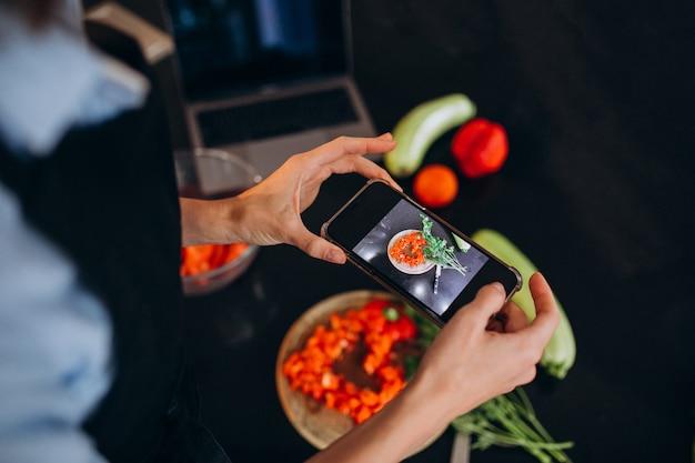 Frau, die foto von einer mahlzeit an ihrem telefon macht Kostenlose Fotos