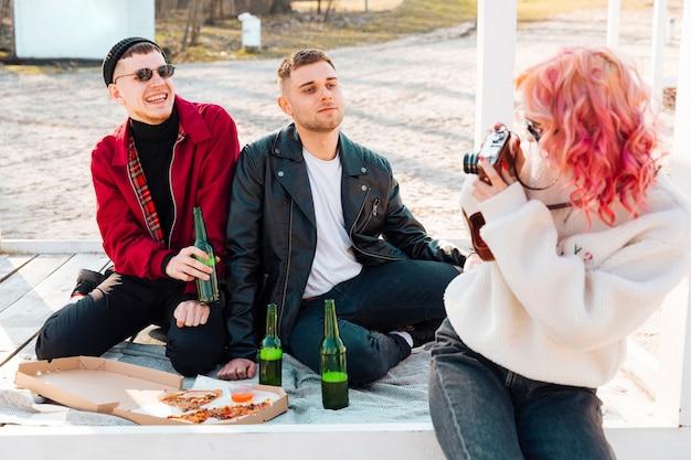 Frau, die foto von lächelnden paaren vom mann auf picknick macht Kostenlose Fotos