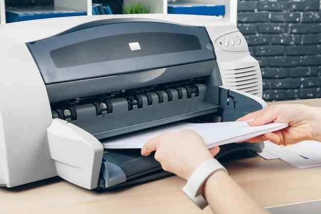 Frau, die fotokopie unter verwendung des kopierers im büro macht Premium Fotos