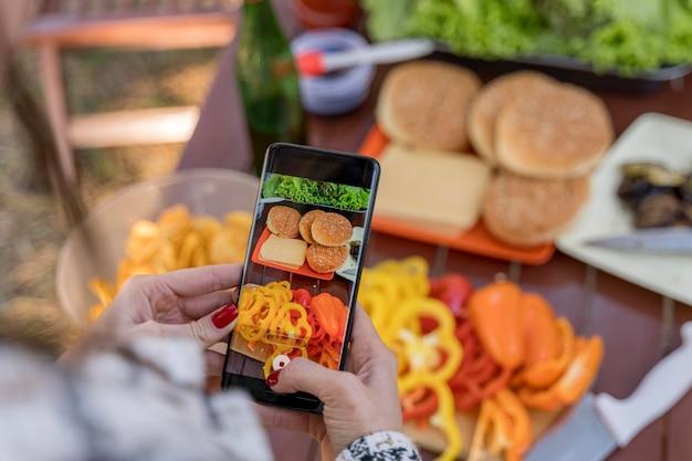 Frau, die fotos des essens beim grillen mit freunden macht Premium Fotos