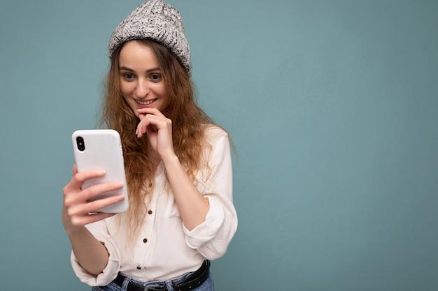 Frau, die freizeitkleidung trägt, die isoliert über hintergrundsurfen im internet steht Premium Fotos
