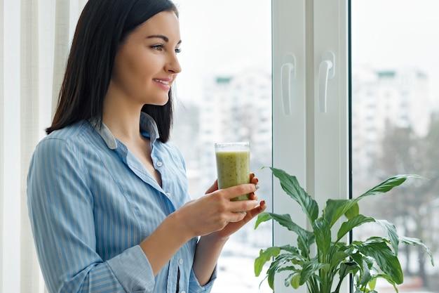Frau, die frisch gemischten grünen kiwi smoothie trinkt Premium Fotos