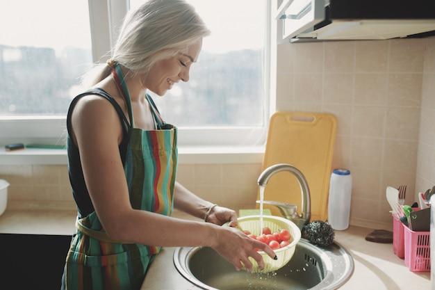 Frau, die frischgemüsetomaten in der küche unter wasserstrom wäscht Kostenlose Fotos