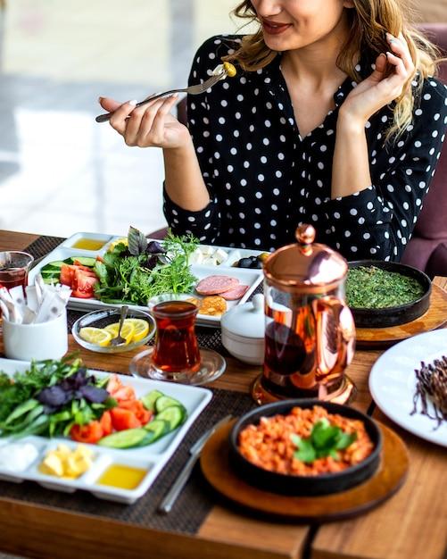 Frau, die frühstücks-rührei mit kräutergemüsekräutern und tee isst Kostenlose Fotos