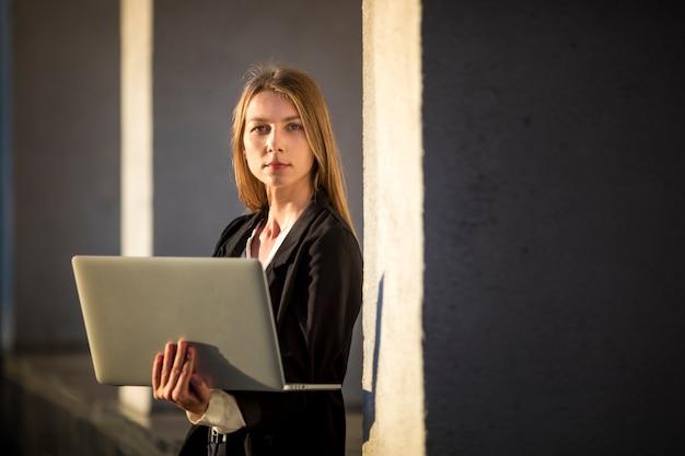 Frau, die für die kamera hält einen laptop aufwirft Kostenlose Fotos
