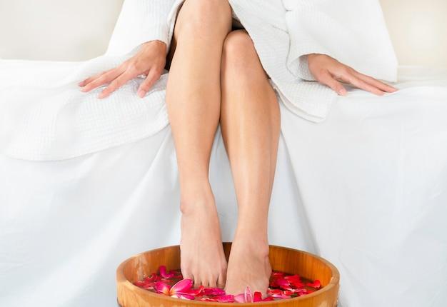 Frau, die füße in der hölzernen badekurortschüssel wasser mit sich hin- und herbewegenden blumen am badekurort tränkt. Premium Fotos
