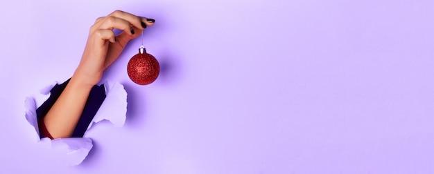 Frau, die funkelnden roten weihnachtsball über purpurrotem hintergrund hält Premium Fotos