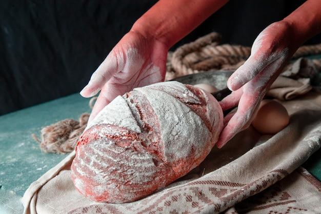 Frau, die ganzes selbst gemachtes brot mit den händen auf das braune tuch setzt. mehl auf dem brot. Kostenlose Fotos
