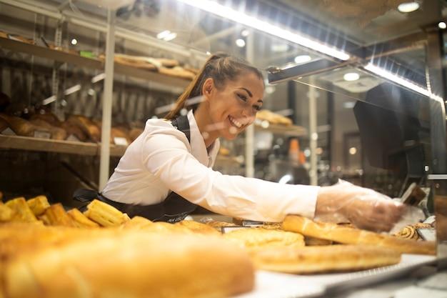 Frau, die gebäck für verkauf in der supermarktbäckereiabteilung vorbereitet Kostenlose Fotos
