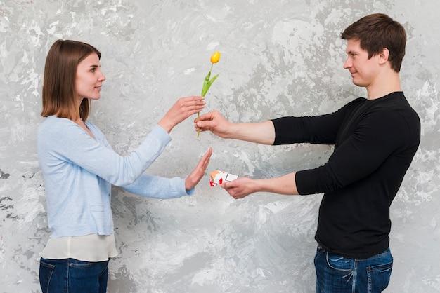 Frau, die gelbe tulpenblume und nein zum zigarettenpaketangebot vom gutaussehenden mann annimmt Kostenlose Fotos
