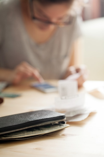 Frau, die geld an ihrem telefon zählt Kostenlose Fotos