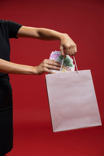 Frau, die geld in ihre einkaufstasche einsetzt Kostenlose Fotos