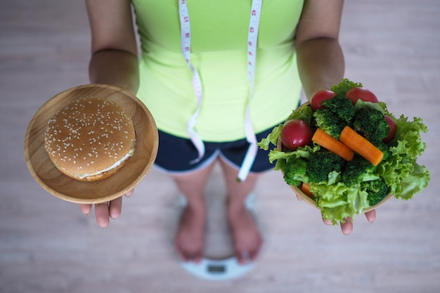 Frau, die gemüseteller mit hamburger wiegt und hält. essen Premium Fotos