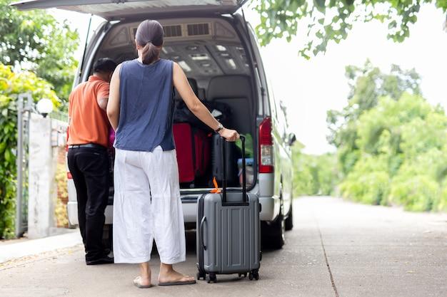 Frau, die gepäck mit dem fahrer einsetzt gepäck in minibusreisekonzept hält. Premium Fotos