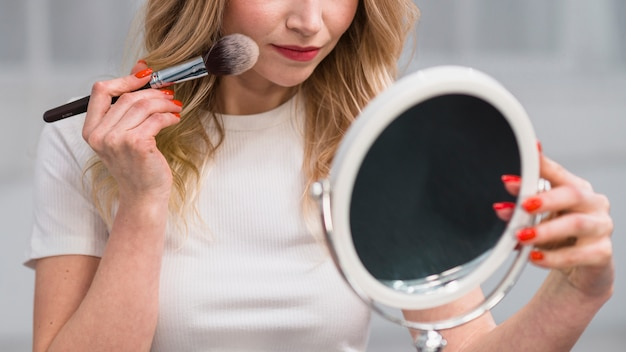 Frau, die gesicht beim spiegeln pulverisiert Kostenlose Fotos