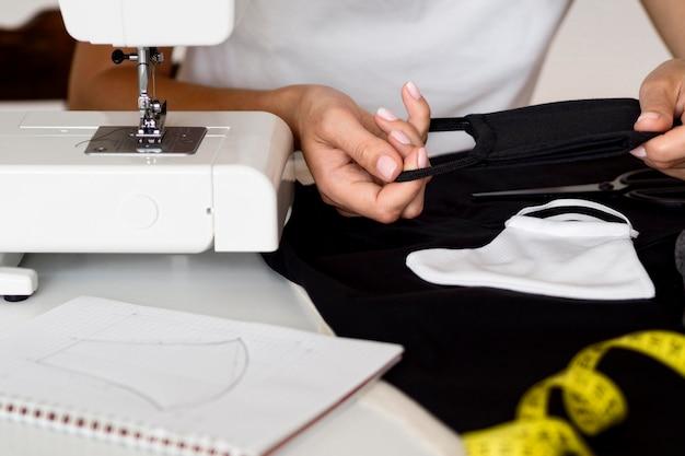Frau, die gesichtsmaske aus textil näht Kostenlose Fotos
