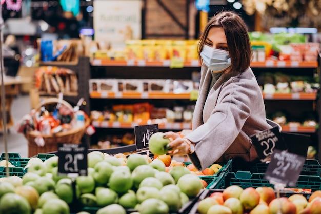 Frau, die gesichtsmaske trägt und im lebensmittelgeschäft einkauft Kostenlose Fotos