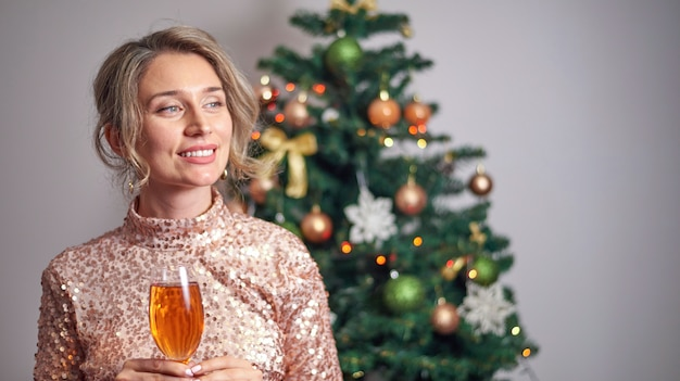 Frau, die glas champagner mit weihnachtsbaum hält Premium Fotos
