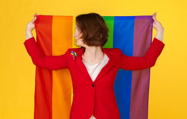 Frau, die große lgbt-flagge hält und wellenartig bewegt Premium Fotos