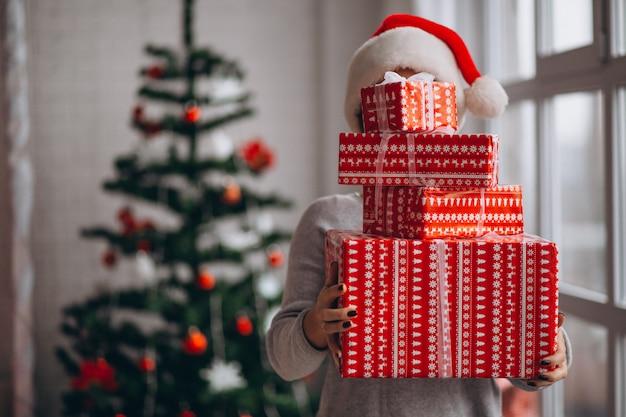 Frau, die große weihnachtskästen hält Kostenlose Fotos