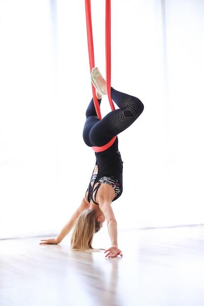 Frau, die gymnastikpilates mit rotem leinen tut Kostenlose Fotos