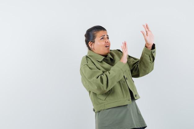 Frau, die hände auf schützende weise in jacke, t-shirt anhebt und ängstlich aussieht. Kostenlose Fotos