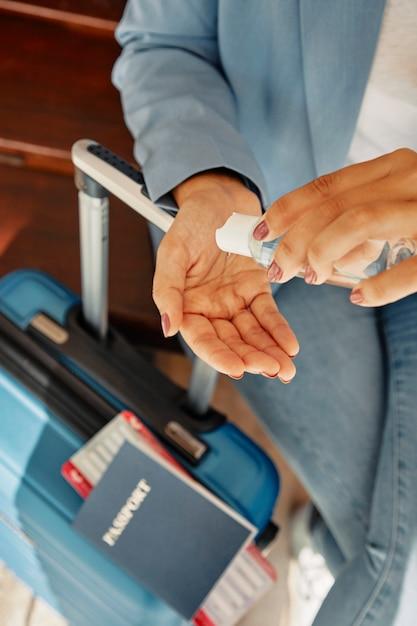 Frau, die händedesinfektionsmittel während am flughafen mit gepäck während der pandemie verwendet Premium Fotos