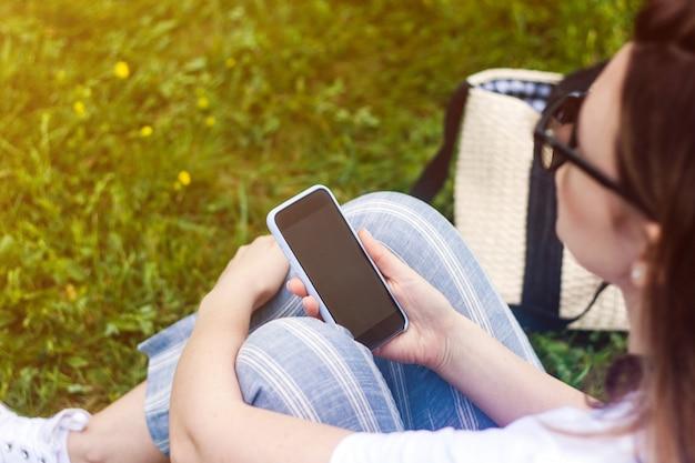 Frau, die handy mit dunklem schirm in ihrer hand hält. Premium Fotos