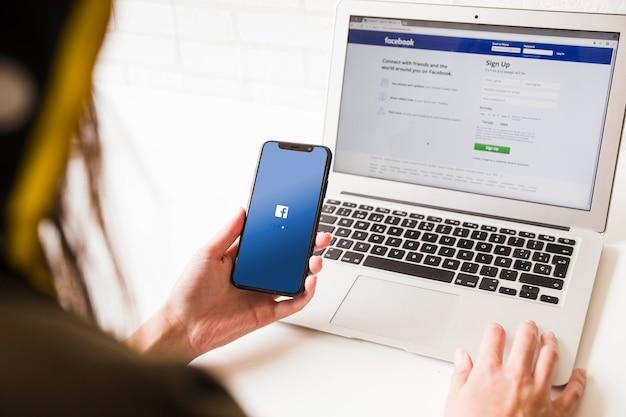 Frau, die handy mit facebook-anwendungshomepage betrachtet Kostenlose Fotos