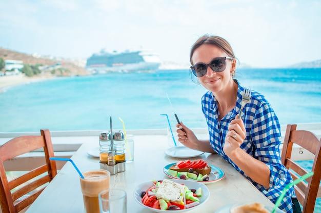 Frau, die heißen kaffee auf luxushotelterrasse mit seeansicht am erholungsortrestaurant trinkt Premium Fotos