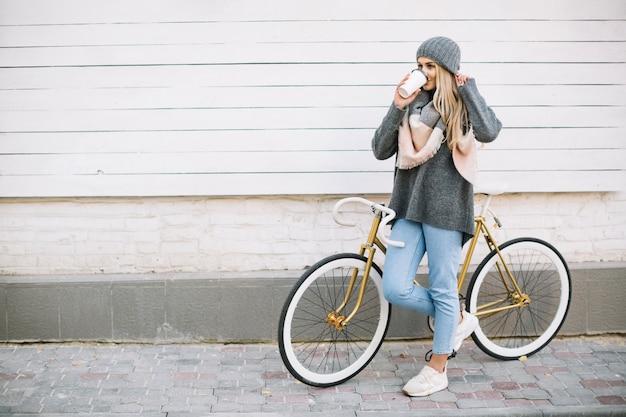 Frau, die heißgetränk nahe fahrrad trinkt Kostenlose Fotos