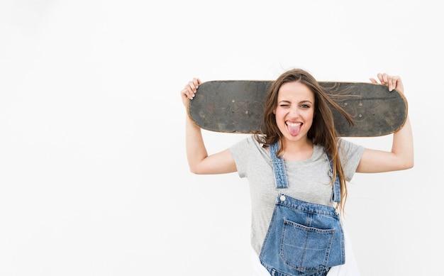 Frau, die heraus ihre zunge heraushalten skateboard auf ihrer schulter gegen weißen hintergrund haftet Kostenlose Fotos