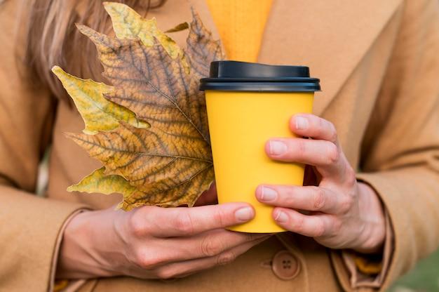 Frau, die herbstblätter und eine tasse kaffee hält Kostenlose Fotos