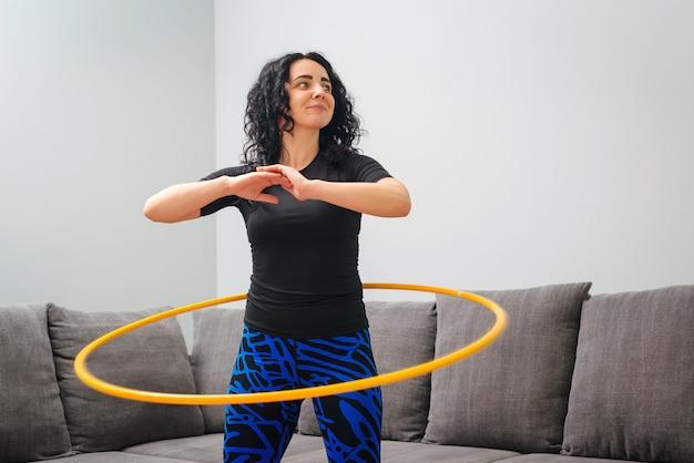 Frau, die hula hoop dreht. mädchen trainieren zu hause. gesunder sportlicher lebensstil. Premium Fotos