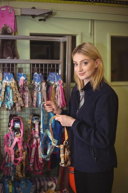 Frau, die hundehalsbänder im geschäft hält Kostenlose Fotos