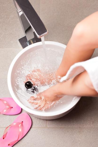 Frau, die hydrotherapiewasserfußbad hat Premium Fotos