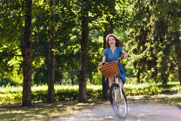 Frau, die ihr fahrrad im wald reitet Kostenlose Fotos