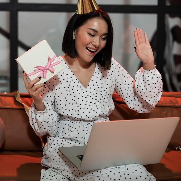 Frau, die ihr geschenk zeigt, während video-chat auf einer silvesterparty Kostenlose Fotos