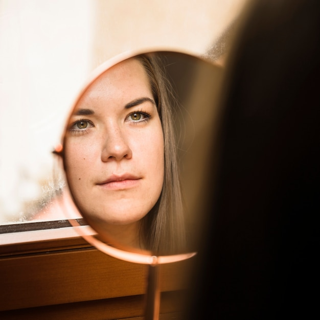 Frau, die ihr gesicht im spiegel betrachtet Kostenlose Fotos