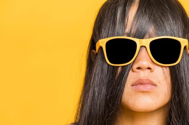 Frau, die ihr gesicht mit dem haar und sonnenbrille bedeckt Kostenlose Fotos