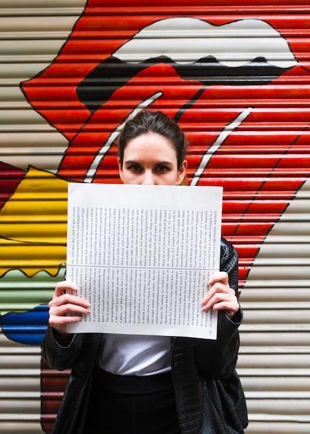 Frau, die ihr gesicht mit papier bedeckt Kostenlose Fotos