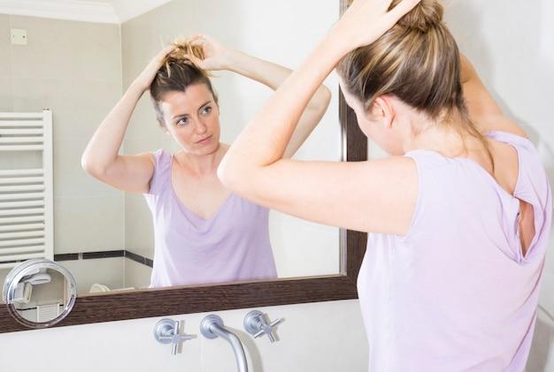 Frau, die ihr haar betrachtet spiegel im badezimmer bindet Kostenlose Fotos